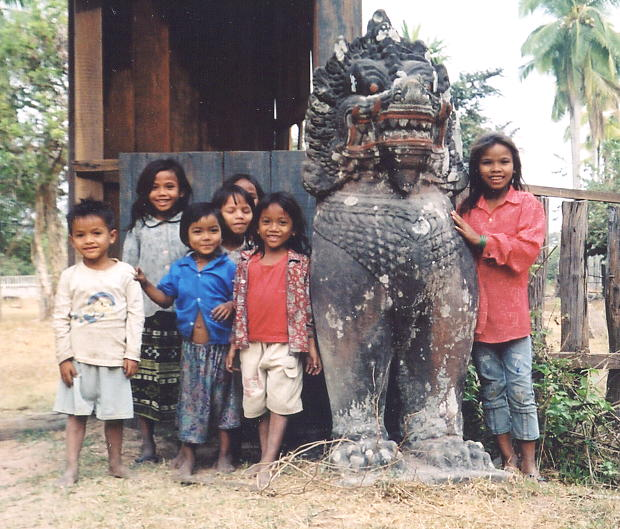 A group of adorable kids and an original lion from Preah Khan, in the village of Ta Seng.