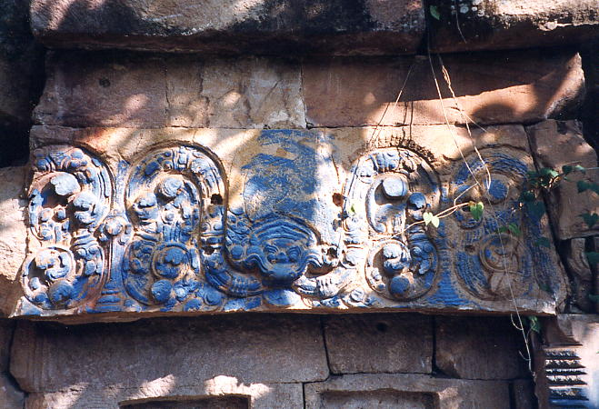 This blue painted lintel shows a carved kala monster and floral patterns but is unfinished.