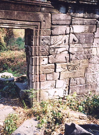 A bas relief carving of a warrior and a chariot next to a doorway into the  main site.