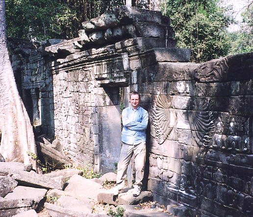 The wall containing two multi-armed Lokesvara carvings, and the author.