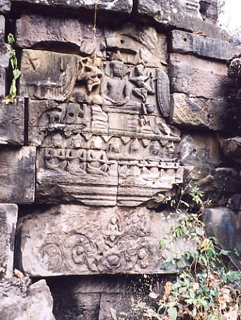 Buddha and his attendants on a pediment above a defaced lintel.