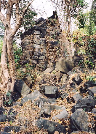The remains of Prasat Toch, covered in dense vegetation.