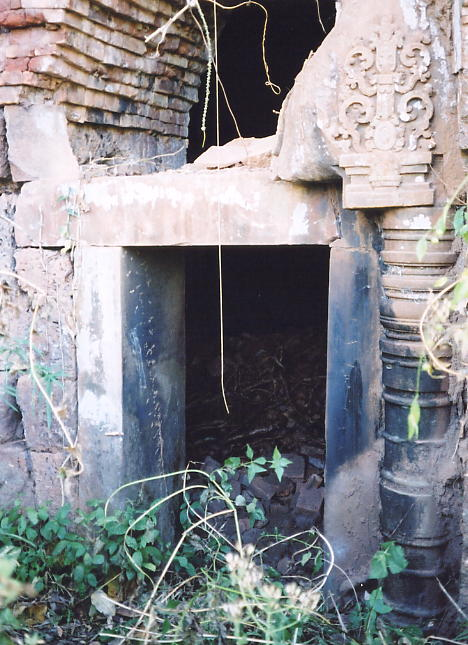 A sandstone doorway with intricate carving and a rounded colonette.