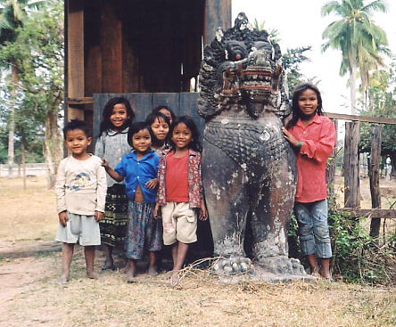 Adorable children and a stone lion in the village of Ta Seng.