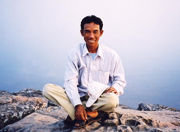 Sokhom, in good spirits, at the cliff-edge with Cambodia spread below him.