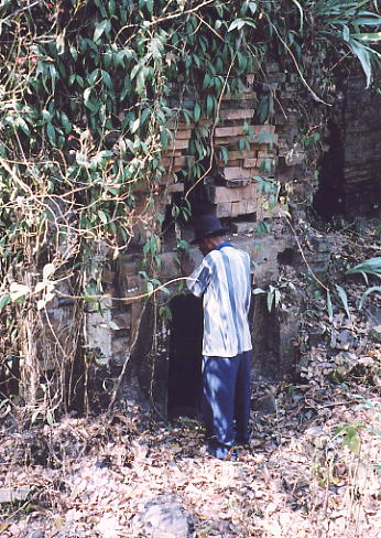 Tomrin inspects one of the brick towers at Prasat Bangkoy South.
